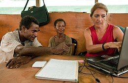 Uriay missionary and tribal couple look at computer