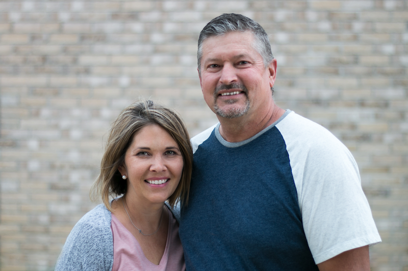 Pete and Lesley standing in front of a brick wall