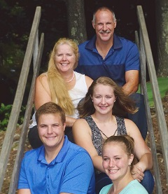 family of 5 sitting on wooden steps