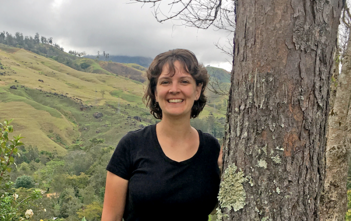 Kristen standing by a tree with a Papua New Guinea mountain valley in the background