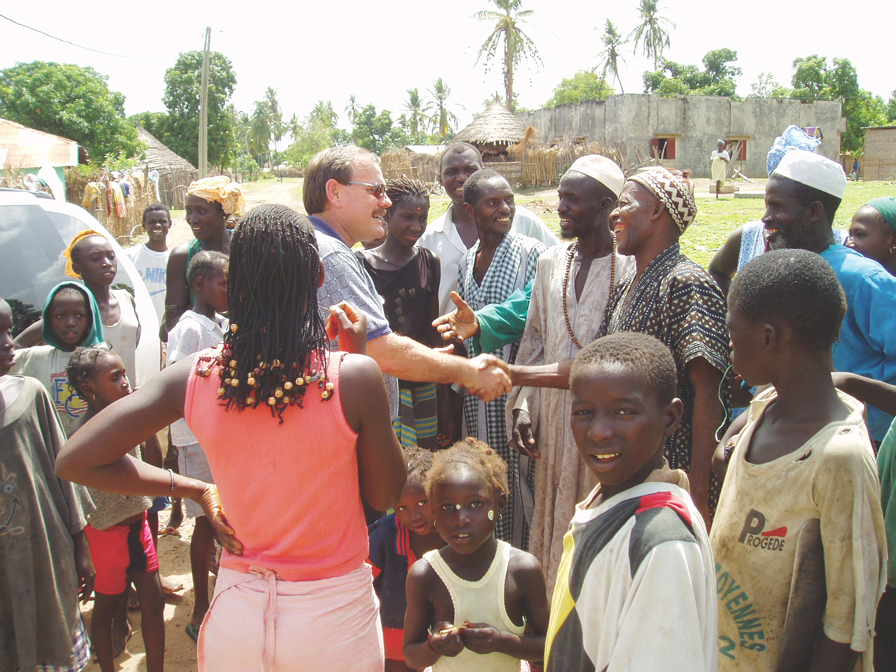 Missionary Dan Rabe shaking hands with Manjack man, with group in village