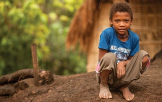 Young boy crouching on ground