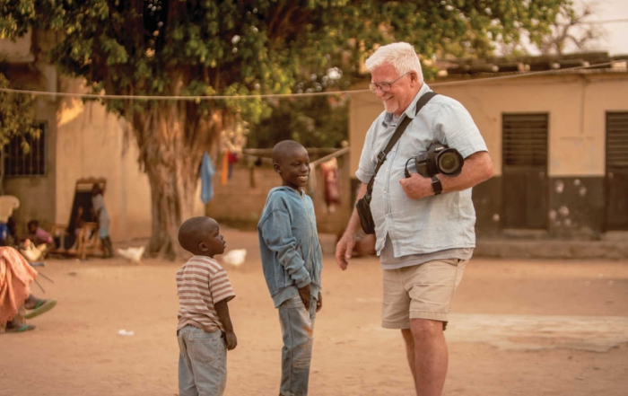man with camera talks to African boys