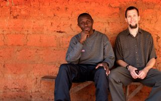 missionary and African man sitting by a red brick wall