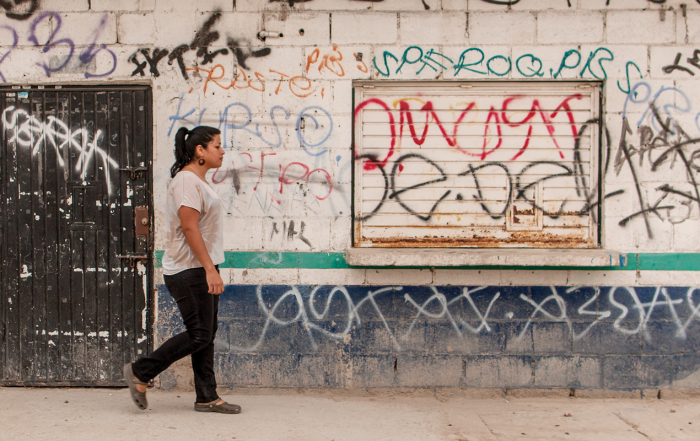 Girl walking in front of wall with graffiti