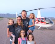 man and woman with their 4 daughters in Arizona with a helicopter in the background