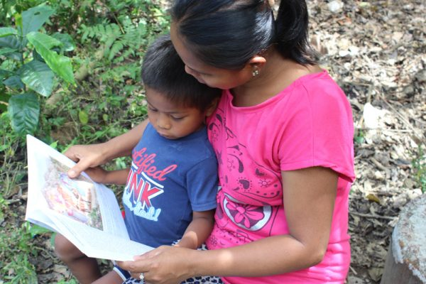 Isnag mother reading Bible story book