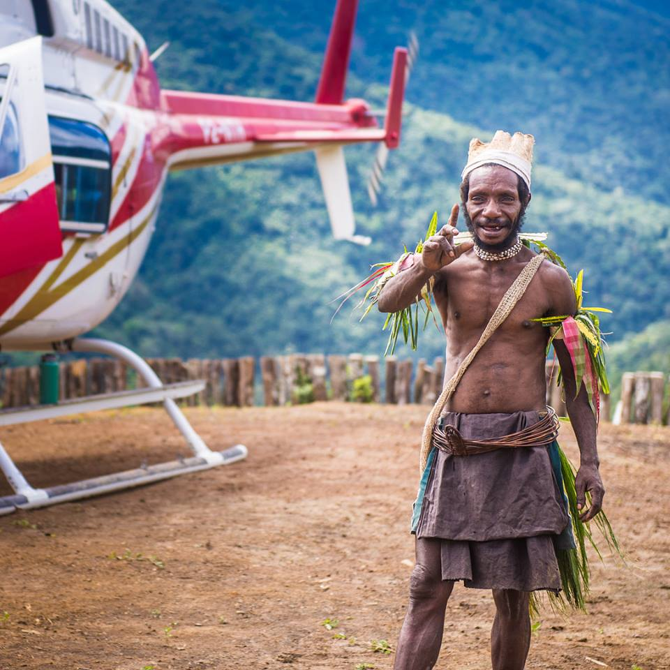 man from Papua New Guinea in traditional garb posing for a picture at a mountain helipad
