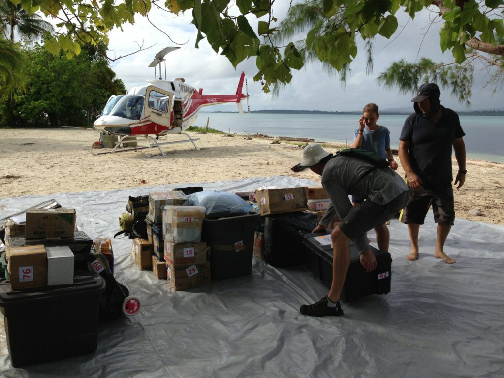 missionaries organize cargo on a beach with helicopter in the background
