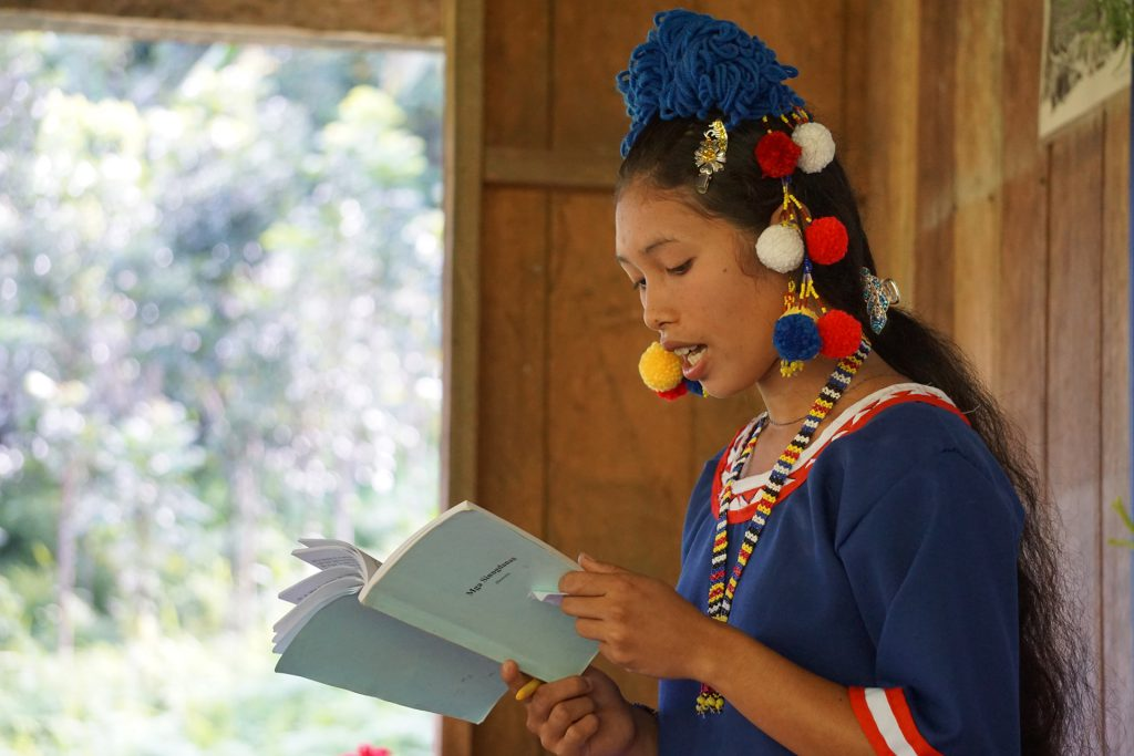 a Tala-andig graduate reads from a portion of the Bible in her own language
