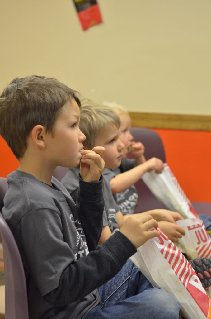 kids watching mission aircraft at work in the Mission Theatre – complete with popcorn