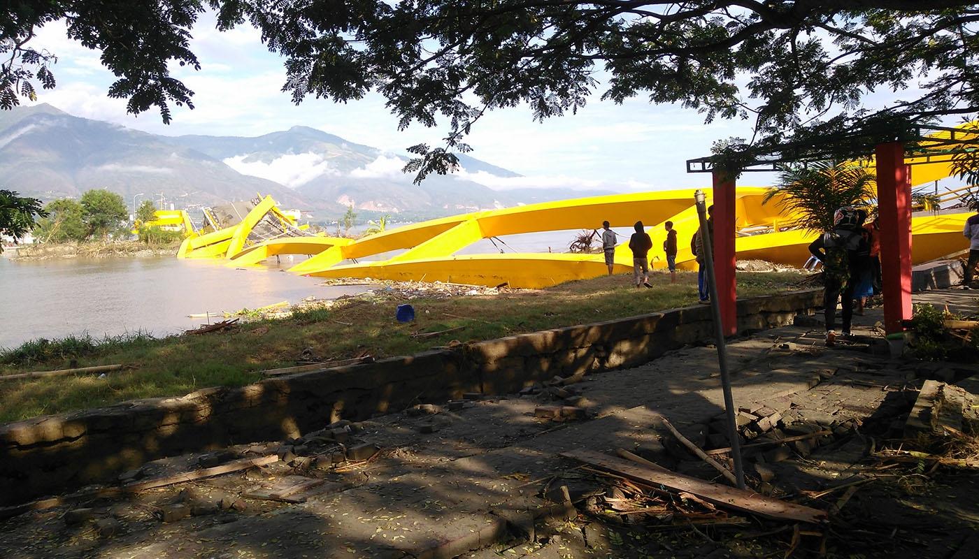 men survey a collapsed bridge in Asia-Pacific