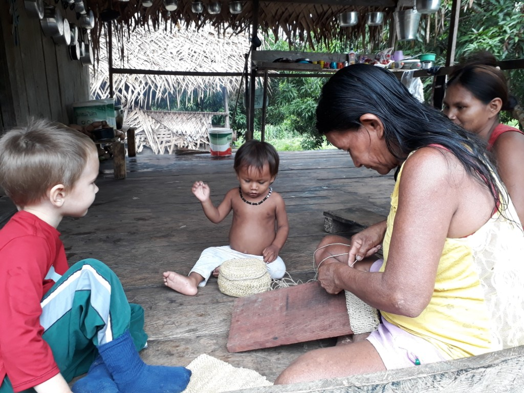 missionary's child sits with locals in a grass hut