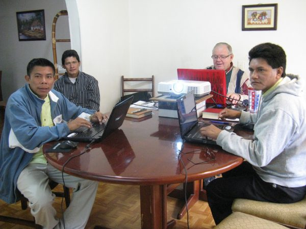 missionary and language helpers translating Bible portion in a house at a table