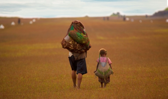 woman and child carrying goods in string bags