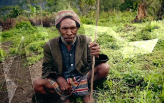 Papua New Guinean man squatting beside a trail in the mountains