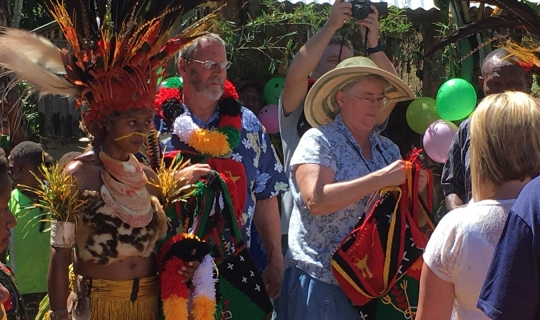 aged missionaries at a Bible dedication ceremony with their friends