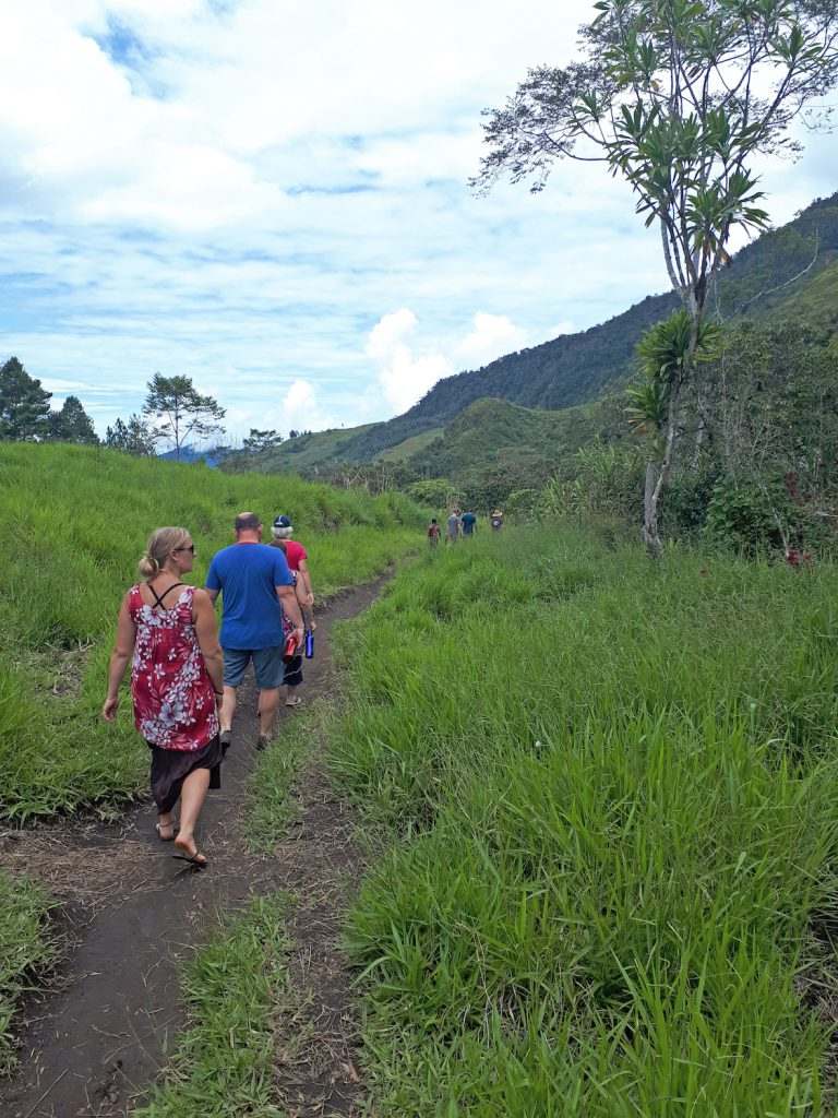 missions trip team members walking along a trail with jungle covered mountain in the background
