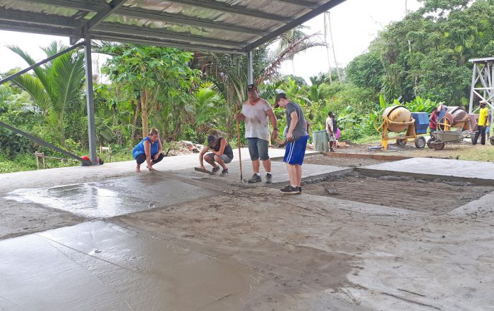 missions trip team members pouring a concrete floor for a building