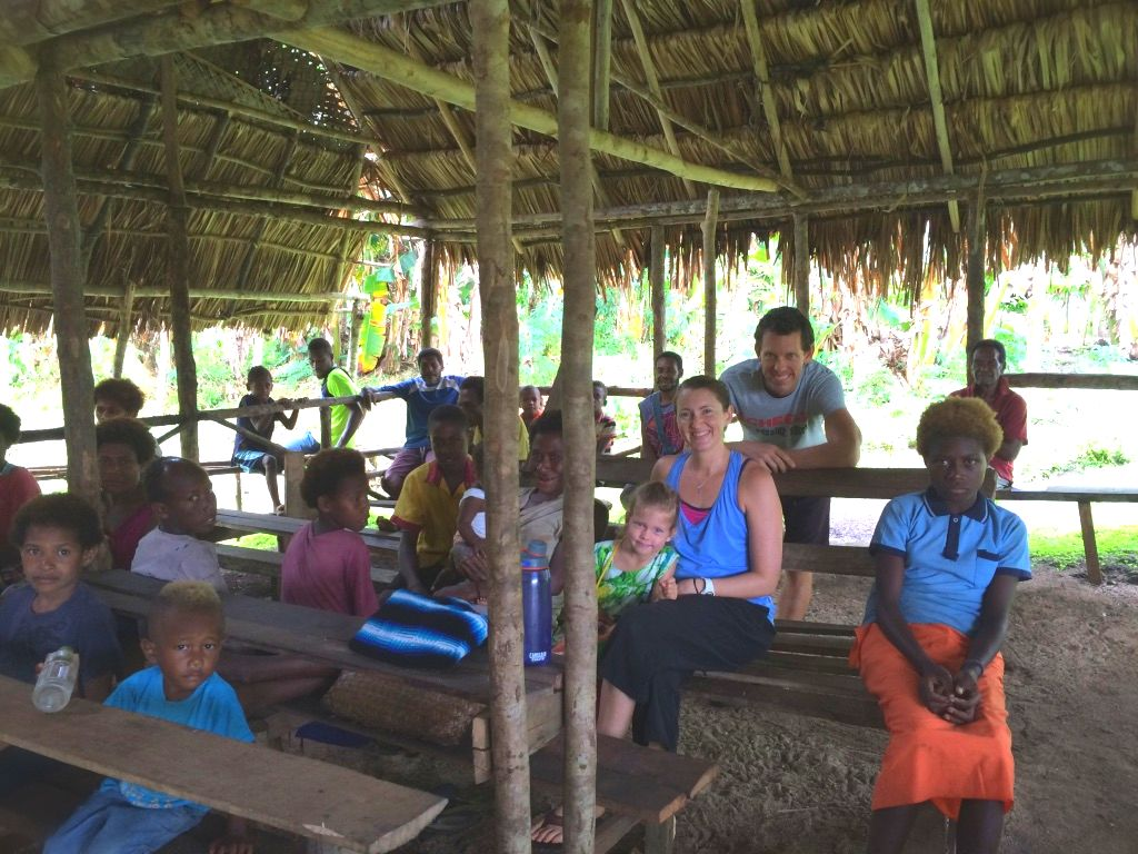 missionaries with locals under a grace roofed shelter