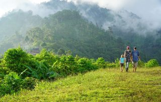 missionary woman and her kids walking near the edge of a mist shrouded valley in Papua New Guinea