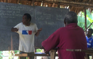 Papua New Guinea man teaching in a hut with no walls