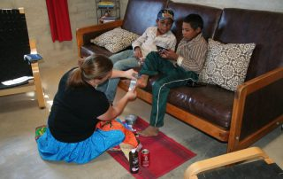 missionary woman serving a boy by bandaging up his foot