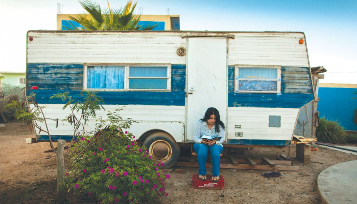 woman reading Bible while sitting on step of her camper trailer