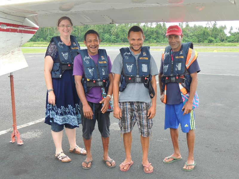 missionary translator with 3 language helpers prepare for a flight in a small plane in Papua New Guinea