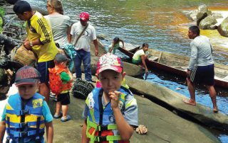 kids and adults on a river bank preparing for a canoe trip