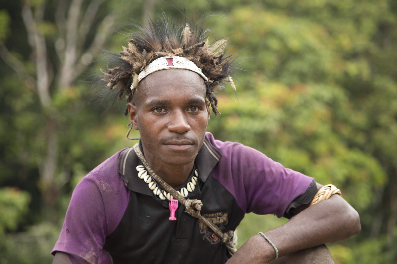 young Papua New Guinean man with feathered hat, bead necklace and string bag