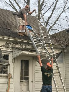 men getting a ladder onto a roof