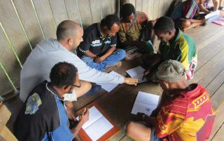 missionary helps tribal men practice their reading