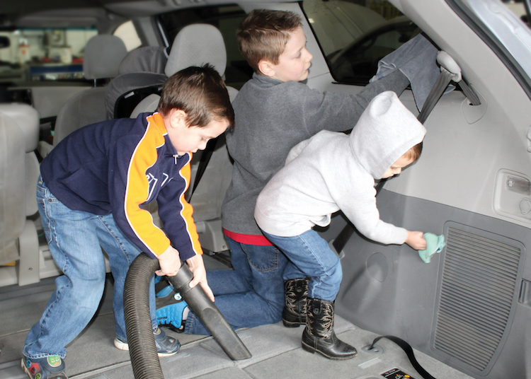 three boys help clean the inside of a van
