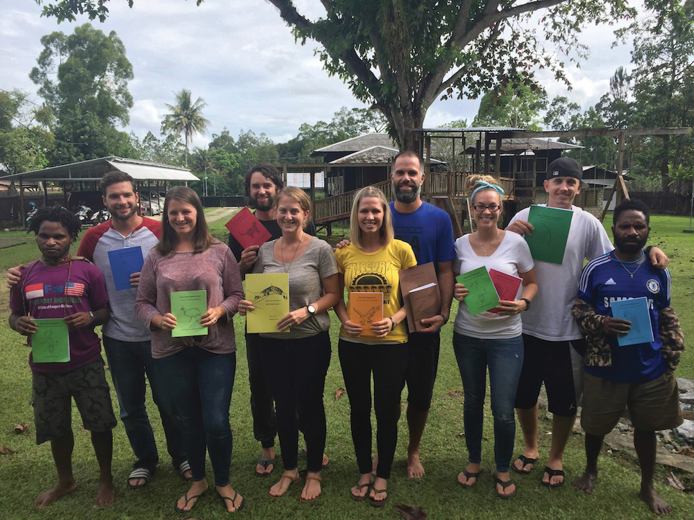team of missionaries and two language helpers holding new reading primers