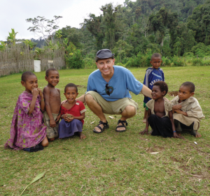 Kevin crouching with some Mibu children in village