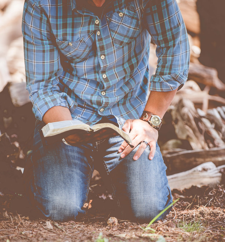 man kneeling on ground and holding Bible