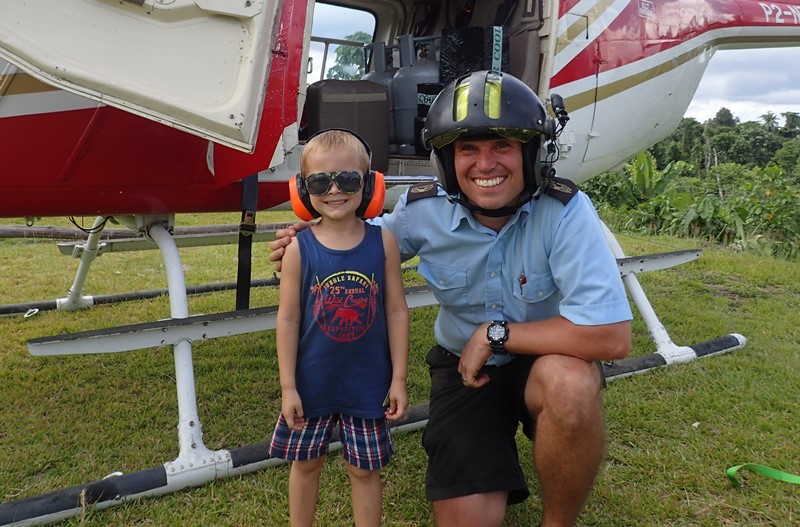 helicopter pilot with child wearing glasses and headphones beside a helicopter