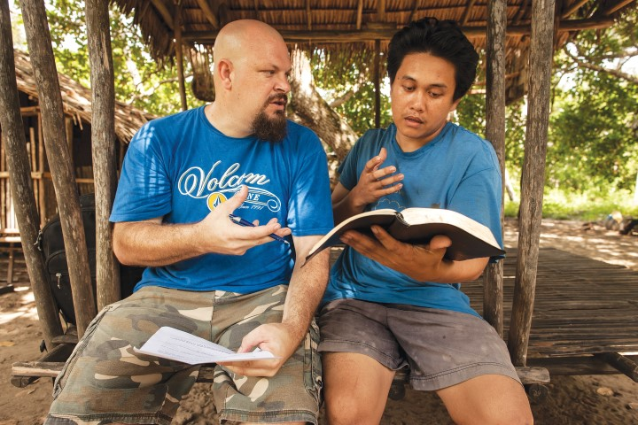 missionary and national man study Bible together