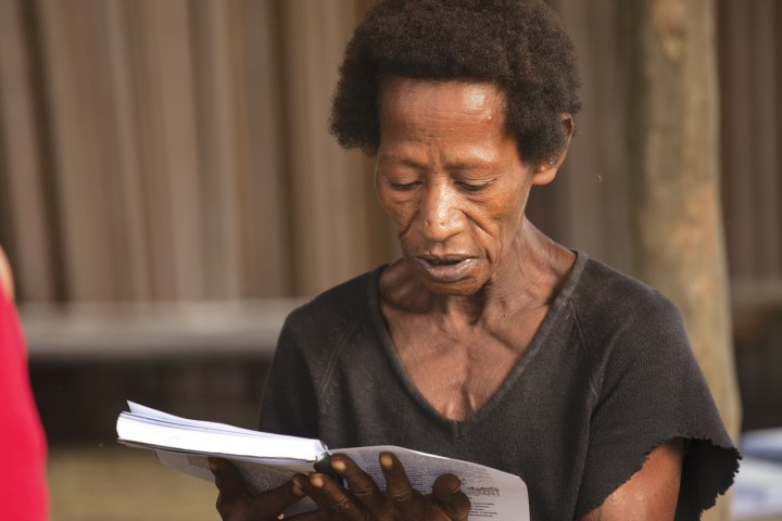 woman reads Bible portion in her own language