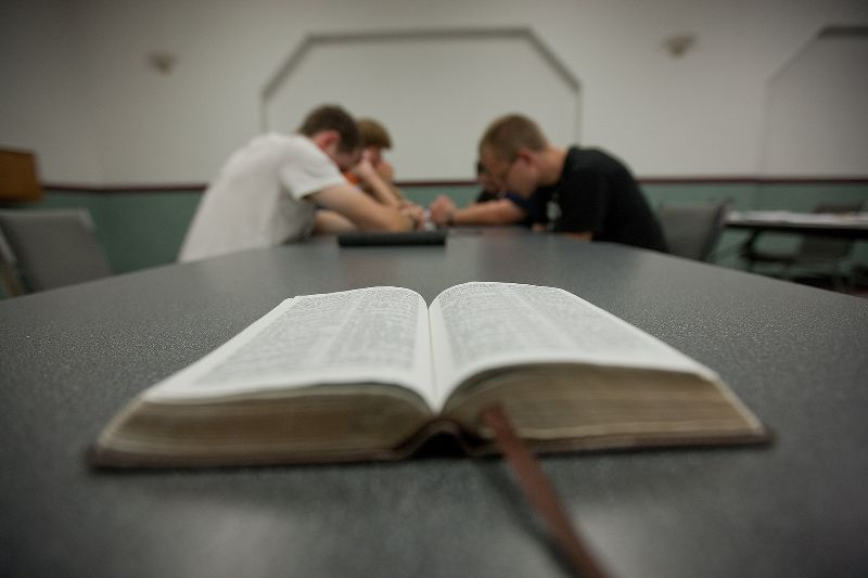 Bible in the foreground; prayer group in the background