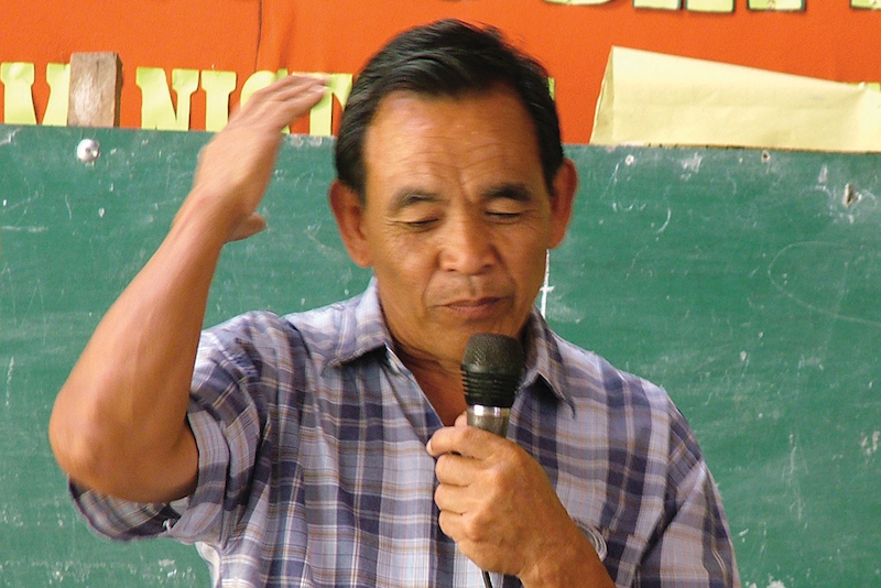 Filipino man speaking at Bible dedication service