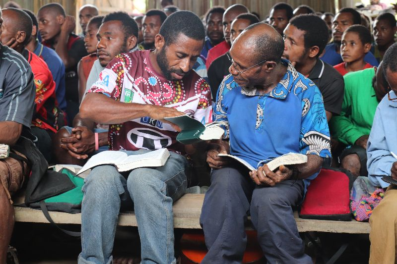 two men study the Bible during a church service