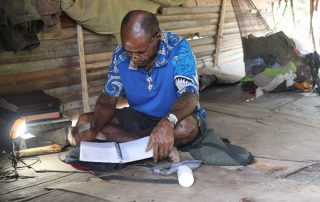Namoleya studying the Bible in his hut
