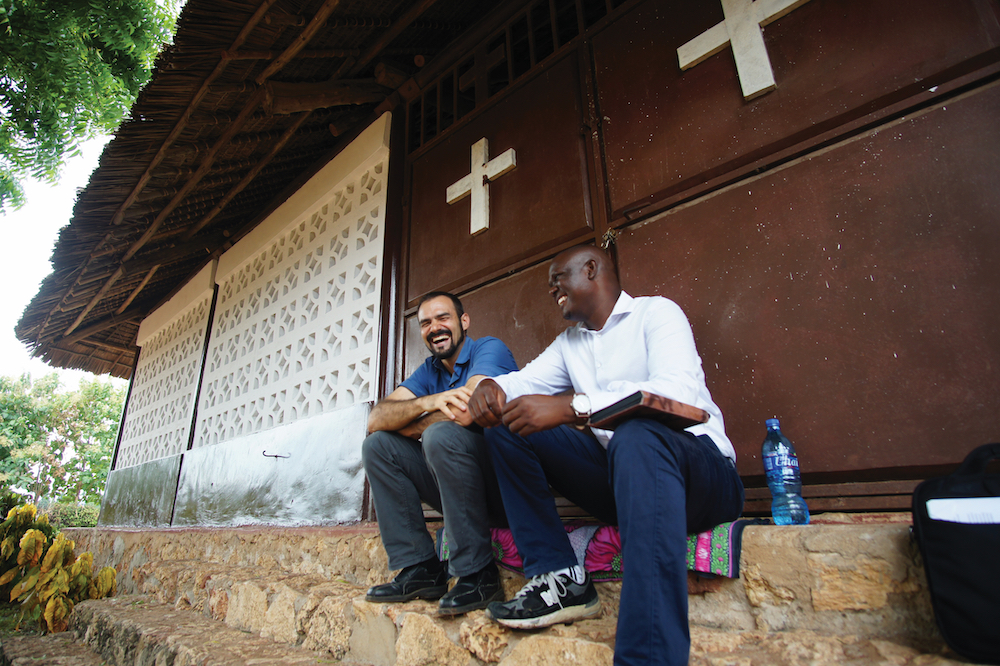 missionary and African pastor joke together outside a church