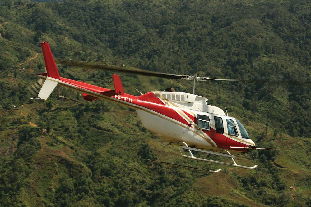 red and white helicopter flying over rugged mountains