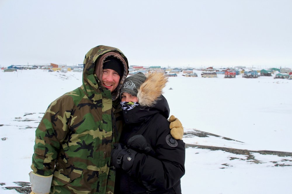 man and woman in snow gear with a northern community in the background