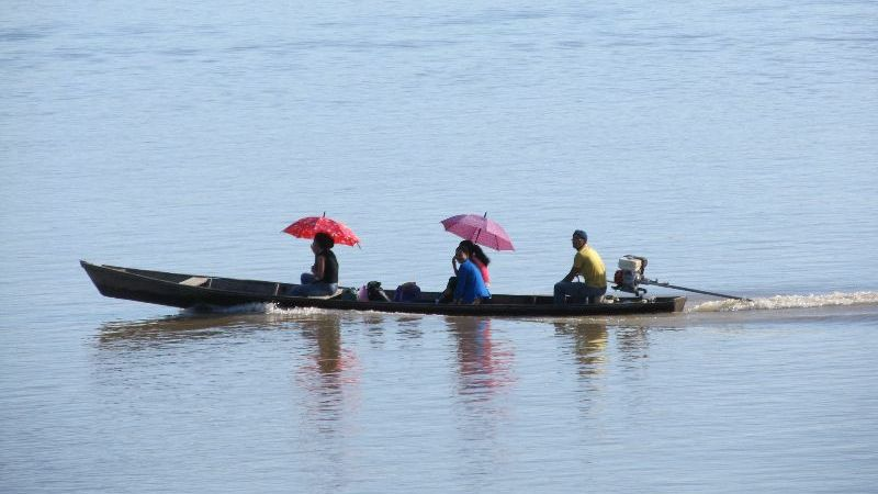 people riding in canoe with umbrellas