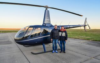pilots standing by new helicopter before leaving for Brazil