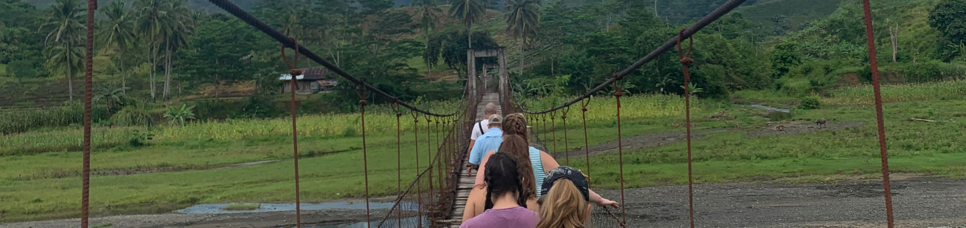 Encounter participants crossing a rope bridge